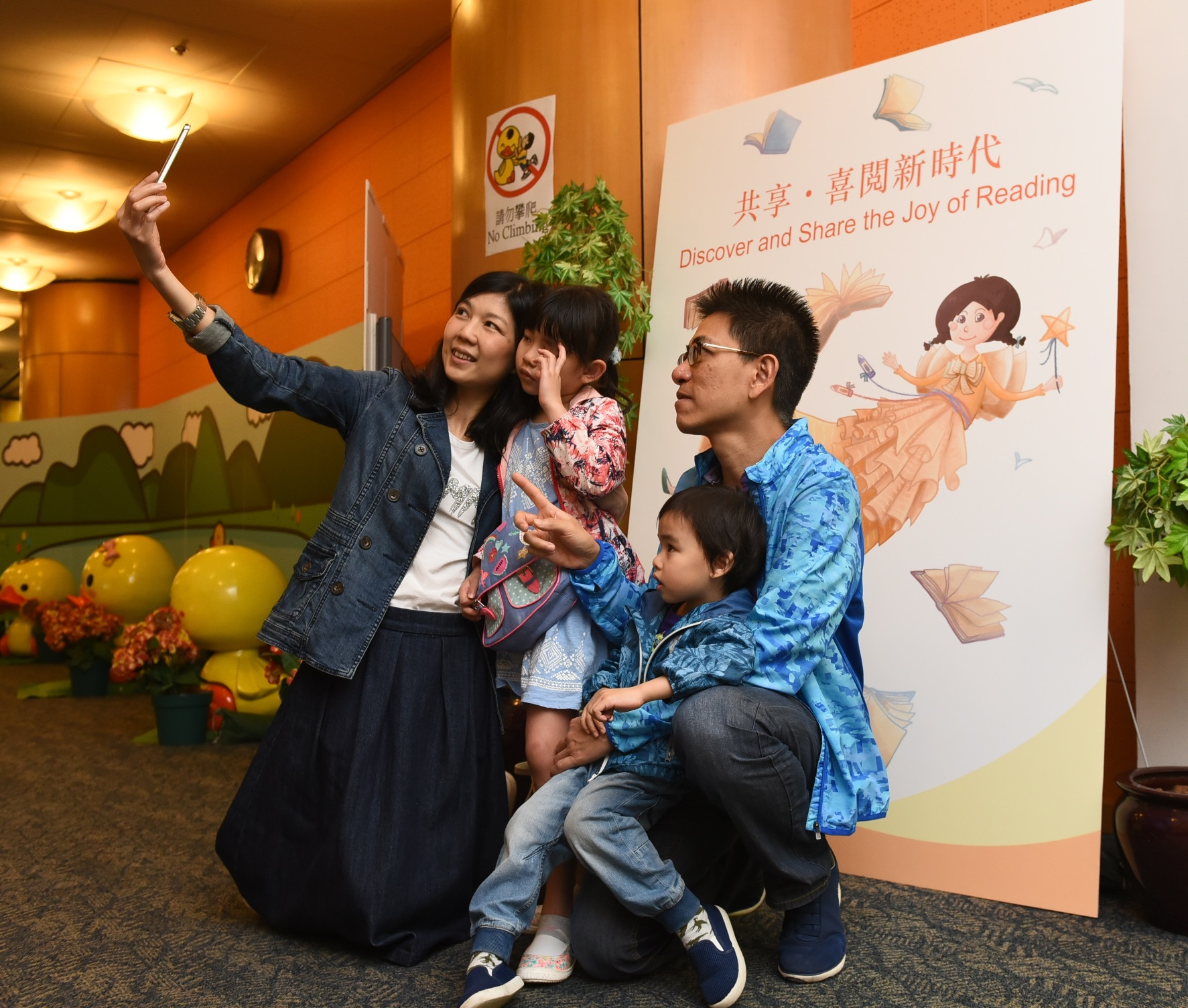 A family selfie with the 'Joy of Reading' Mascot