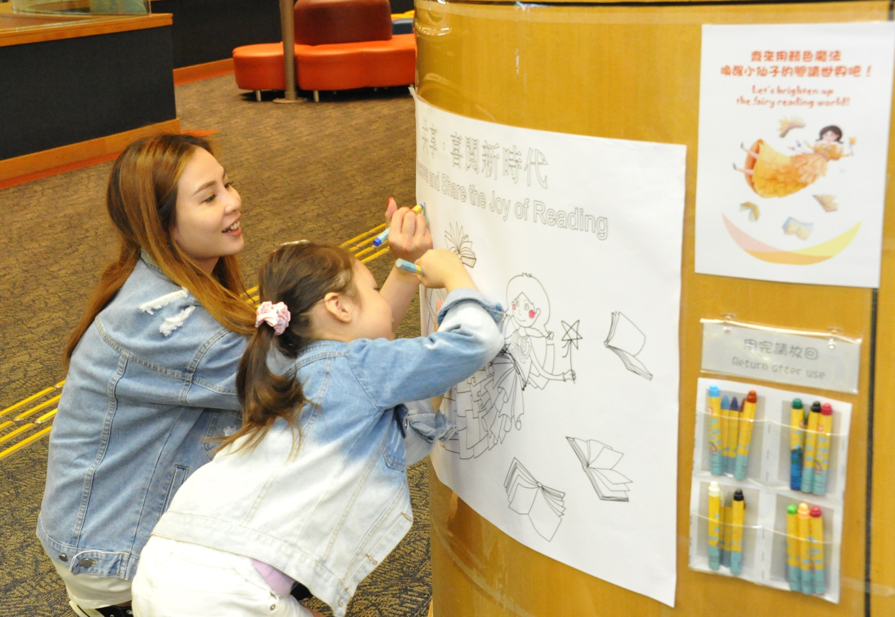 Colouring the 'Joy of Reading' mascot on the library wall